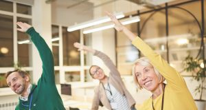 Cheerful active company employees in bright clothing exercising in office and making bending aside