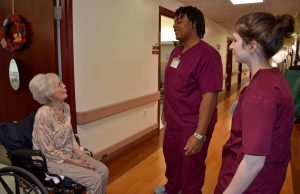 Merle Houston, a resident at A.G. Rhodes, talks with students Elijah Branche and Abby Fishman.