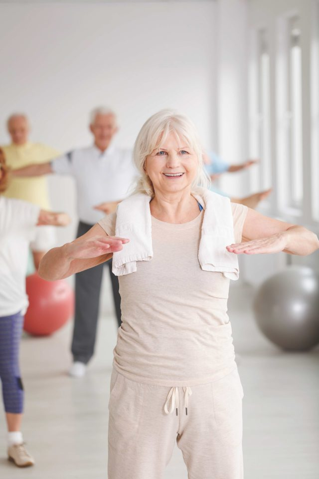 Smiling elder lady with towel stretching at the gym