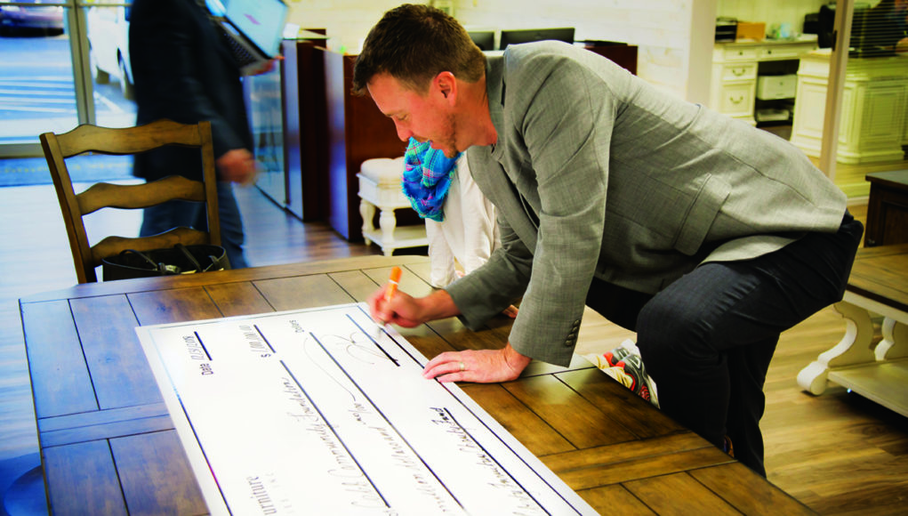 Liberty Furniture's Jason Brian signing the check for his company's donor-advised fund.