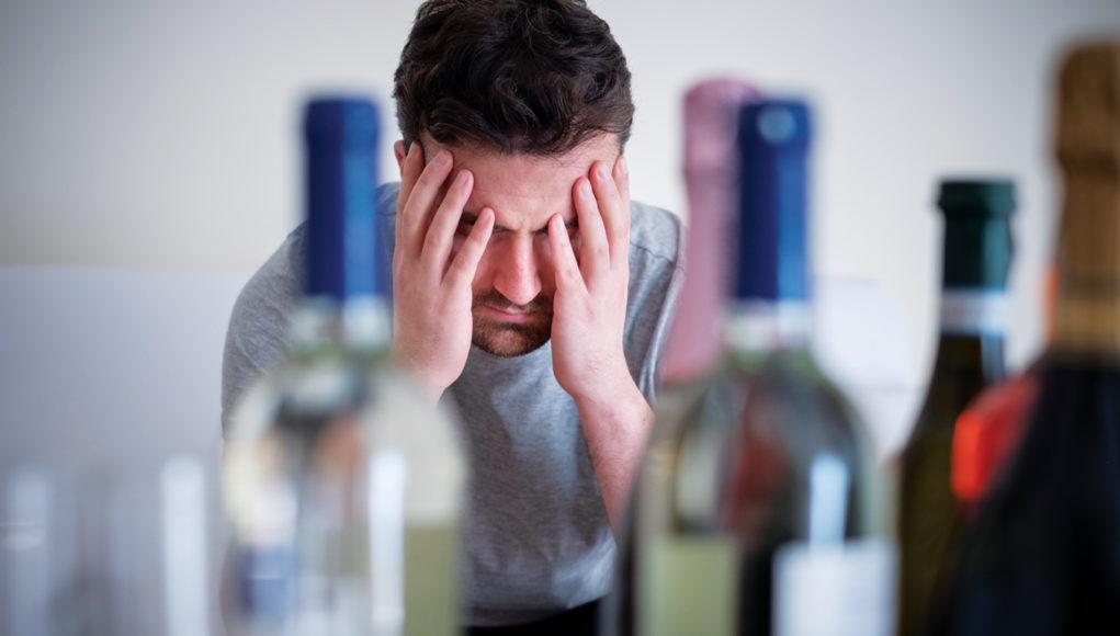 Alcohol addicted man portrait alone with spirit bottle