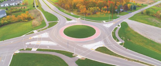 Aerial view of roundabout intersection at first light, with Autumn trees.