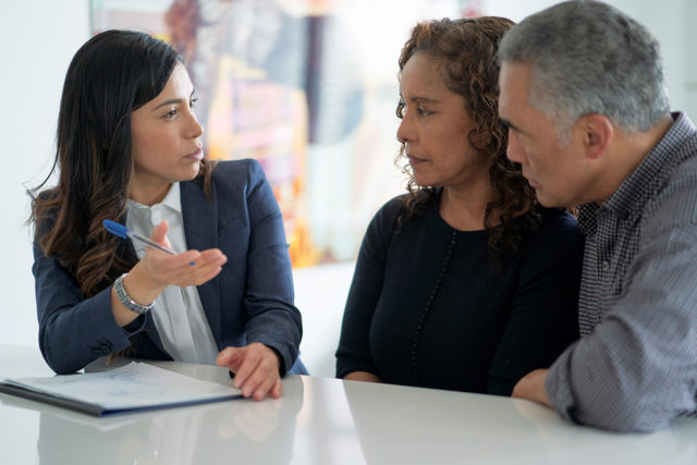 An adviser meets with a mixed race middle-aged couple to discuss their life insurance or financial needs. The couple is dressed casually and the adviser is in a suit. They are seated around the clients kitchen table.