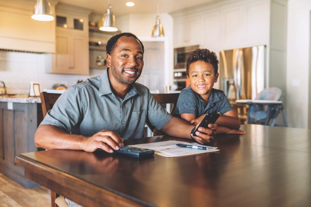 A middle-aged man sits at his dining room table with his young son teaching him about home finances. He is working from home and telecommuting.