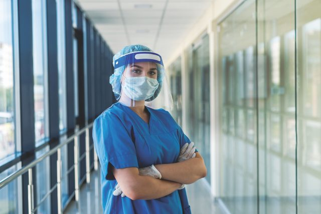 portrait of a young nurse in a blue uniform and a protective shield to protect against a new dangerous virus covid19