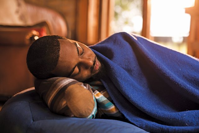 Tired black man lying on a bean bag and sleeping while being covered with blue blanket.
