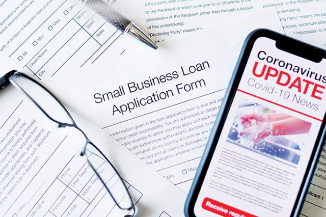 Small business loan application form. Close up of a mobile phone with Coronavirus covid-19 news update. There is a small business loan application in the background on the desk. The phone has an image of hand washing hygiene.