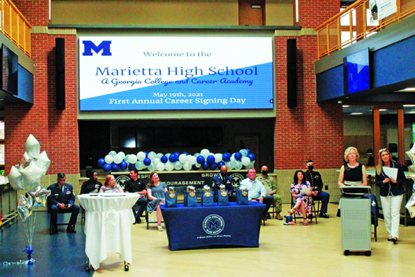 Board members, business partners, and military representatives on Career Signing stage in J Hall (new building at MHS).