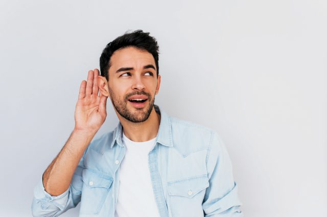 Portrait of handsome interested male placing hand on ear asking someone to speak up, isolated over white background. Young stylish man which overhears conversation in the studio. Copy space for text.